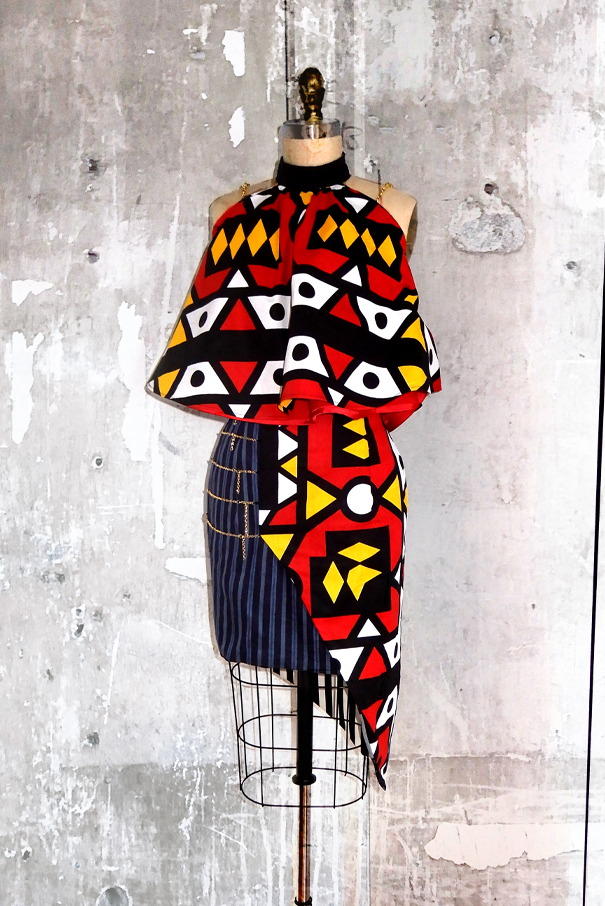 Reverse side of the garment shows red, yellow, and black and white Ankara print on the top and on the skirt.
