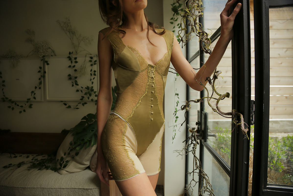 """""""This sage green bodysuit is made from stretch charmeuse, hand-dyed Chantilly lace, and power mesh. The dyed to match lace is appliquéd along the front and sides of the garment. Down the center front are matching silk charmeuse covered buttons that serve as a faux closure. """""""