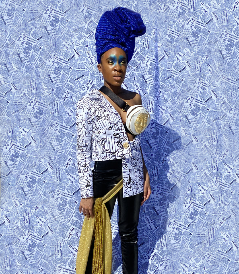 Woman in shimmer blue turban. Abstract black and white print asymmetrical blazer. Black faux leather pants with golden glitter waist sash. Newsprint backdrop. Golden mask fanny pack accessory. Dramatic blue eyeshadow on inner eye lid and inner eyebrows.