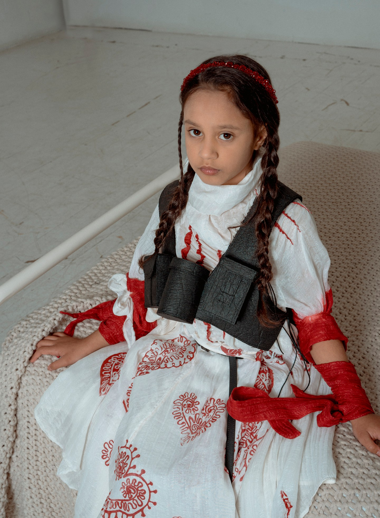 An eight-year-old brown hair wearing a high neck white silk blouse, a red heart pattern printed box pleat skirt, and a black vest, standing sitting on a hospital bed.