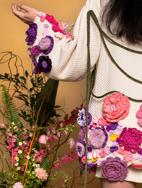 Back view of left side. Left arm extended showing sleeve embellished with yarn flowers in shades of purple. Back left half of body is embellished with purple, yellow, and pink yarn flowers. Green knitted cords hang between the shoulders.