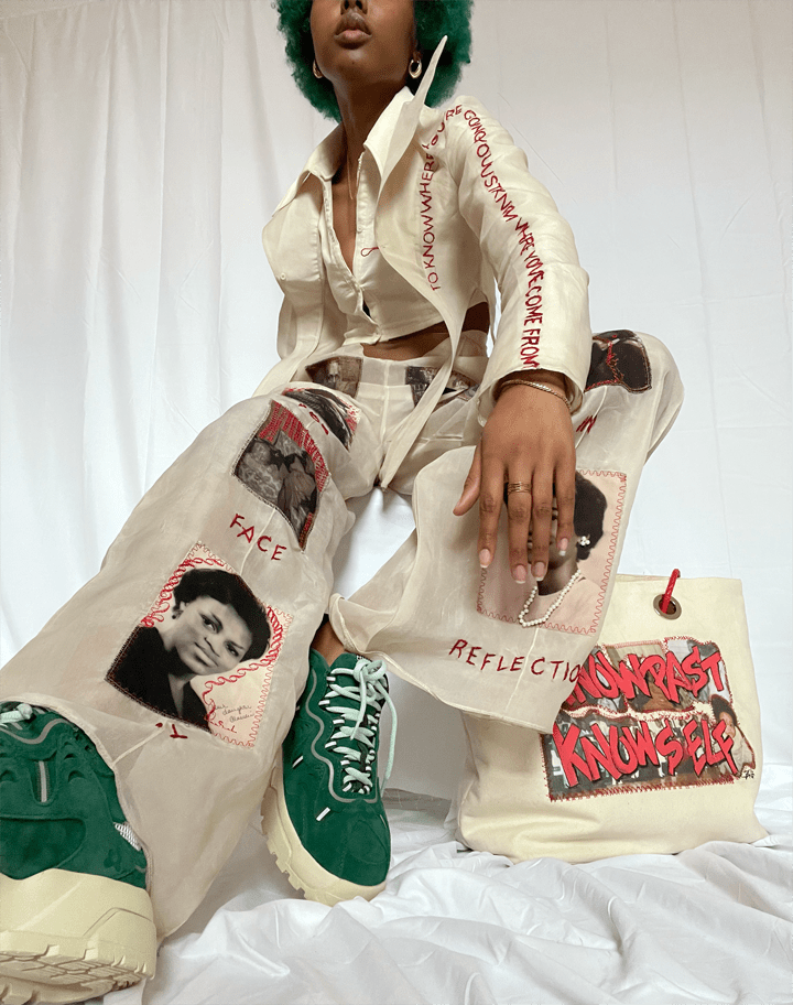 Young woman sitting on chair with a bag beside her. Clothing: unbuttoned beige blazer revealing a ivory seersucker cropped button up underneath. Pants are beige with portrait photos sewn on top of the pant with accents of red embroidery.