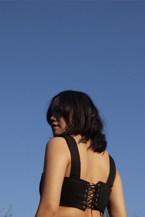 Closeup view of black suede strapless top, showing corset back closing.