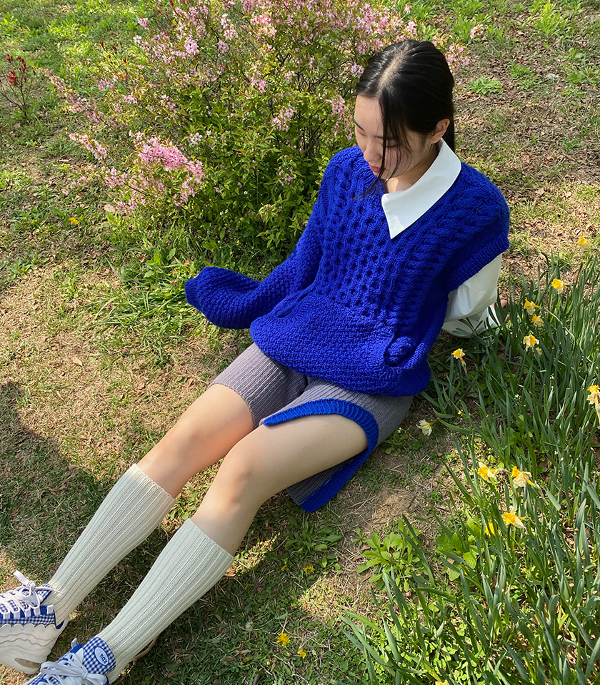 """""""This look is inspired by the personification of youth culture. The model is wearing a hand knit sweater blocked with woven pieces to create a youthful and playful energy. The sweater is completed with a hand crocheted short, finished with a rib cuff for a youthful energy in this look. """""""