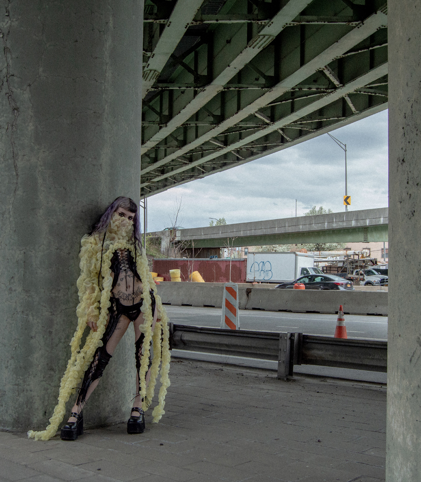 Model standing under a bridge, she wears a chest bind, panty, garter and a yellow cape.