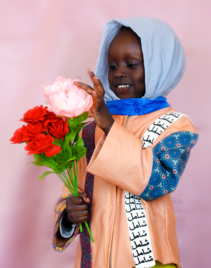 """The child model is holding silk flowers that are red and pink while smiling. The Arabic on the white strap of the jacket reads """"Inclusive""""."""