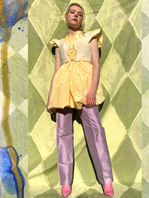Model stands in full figure, wearing rabbit bustier over daffodil dress. Daffodil dress falls above the knee and its gathers spill out of bustier hem. Worn over amethyst trousers, which are stiff, purple silk, with high luster.