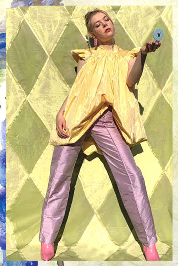 Model wears daffodil dress over amethyst trousers, holding a blue compact mirror with a rabbit embossed on the front. She glances into the mirror in a leaned pose.