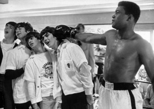 February 18, 1964 - Miami: Boxer Cassius Clay (now Muhammad Ali) taking mock shot at Beatles punching bag quartet (L-R) Paul McCartney, John Lennon, Ringo Starr, and George Harrison, lads grimacing from champ's touch. (Photo by Mike Smith/Pix Inc./The LIFE Images Collection/Getty Images)
