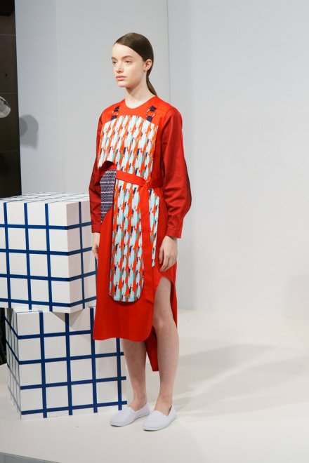 Cassey Gan FW18 London fashion Week An image of a model wearing a primarily red dress with side cutouts and a centre print