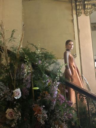 Merchant Archive FW18 LFW A model wearing a pale orange dress on a staircase adorned with wild flowers and heathers