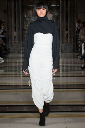 A model wears white over black on the runway for SOE Jakarta at london Fashion Week FW18