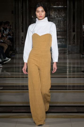 A model wears a mustard bustier jumpsuit over a white polonexk on the runway for SOE Jakarta at london Fashion Week FW18