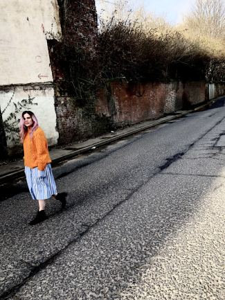 An image of Blogger Pixie Tenenbaum walking in a road wearing a blue and white striped Primark dress with an orange pointelle Topshop jumper on top
