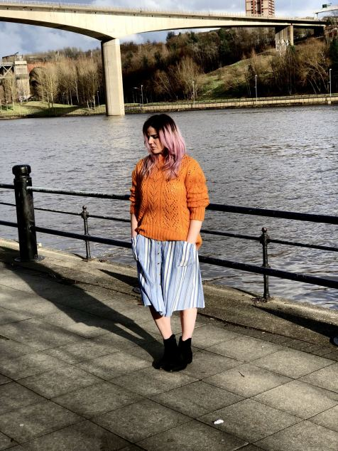 An image of Blogger Pixie Tenenbaum standing by the River Tyne wearing a blue and white striped Primark dress with an orange pointelle Topshop jumper on top