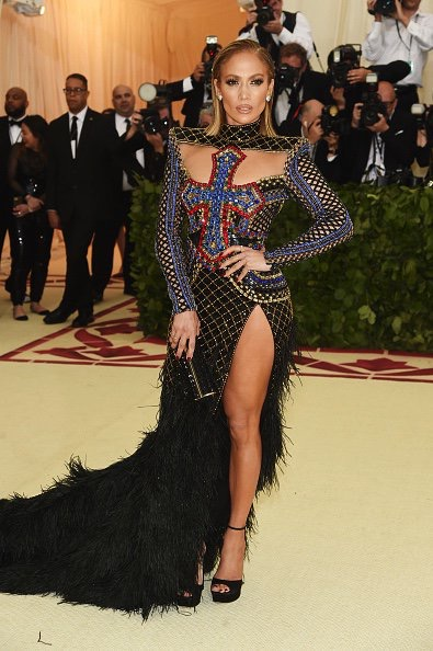 Full length picture of Jennifer lopez on the steps to the met gala wearing a bejewelled split front dress emblazoned with cross detailing