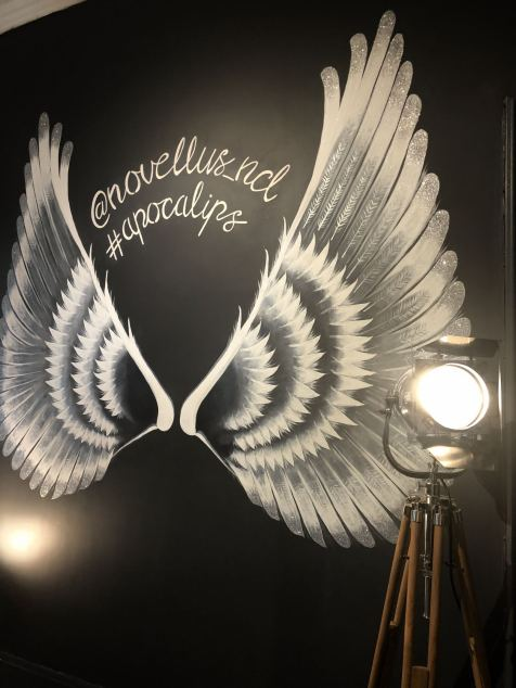 Angel wings painted on a dark grey feature wall in the new Novellus Aesthetics clinic room at 1 Benton Terrace in Jesmond. Glitter tipped wings lit up by a cinema type floor lamp featuring the words Novellus newcastle and #Apocalips. taken for Fashion Voyeur blog