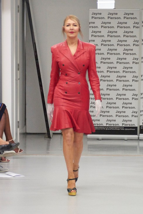 A model on the runway for Jayne Pierson SS19 at London Fashion Week Conde Naste College of Fashion and Design wearing a leather frock coat in red (fashion voyeur blog)