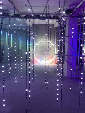 An image taken from the 2018 installation #MulberryLights at 100 Regent Street from fashion brand Mulberry as part of their Christmas campaign featuring some hanging white string lights with a big whiye circle light on a shot blasted brick wall. Fashion Voyeur Blog
