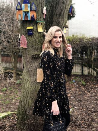 An image of Blogger Pixie Tenenbaum in a park next to a tree decorated with fairy doors. She is wearing a long sleeved cat print midi dress and buckled boots and holding a Lady Dior bag. she is facing the camera and smiling on the day of her 40th birthday ready to go out to dinner