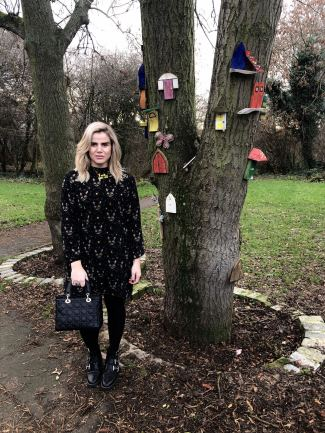 An image of Blogger Pixie Tenenbaum in a park next to a tree decorated with fairy doors. She is wearing a long sleeved cat print midi dress and buckled boots and holding a Lady Dior bag. she is facing the camera on the day of her 40th birthday ready to go out to dinner