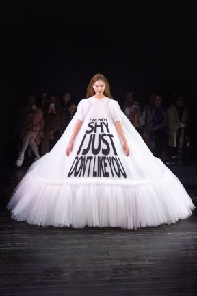 "a model in the Viktor & Rolf Spring 2019 Couture runway show in Paris featuring lots of tulle dresses bearing slogans, this one says ""I'm Not Shy, I Just Don't Like You"""