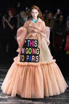 "a model in the Viktor & Rolf Spring 2019 Couture runway show in Paris featuring lots of tulle dresses bearing slogans, this one says ""F*** This I'm Going To Paris"""