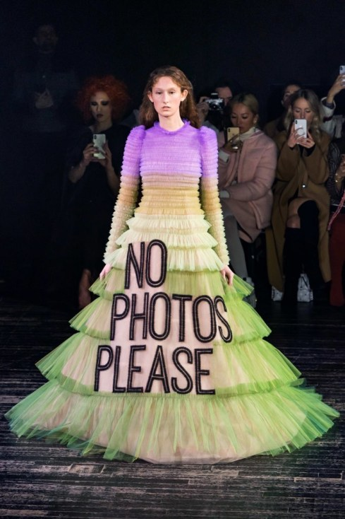 "a model in the Viktor & Rolf Spring 2019 Couture runway show in Paris featuring lots of tulle dresses bearing slogans, this one says ""No Photos Please"""