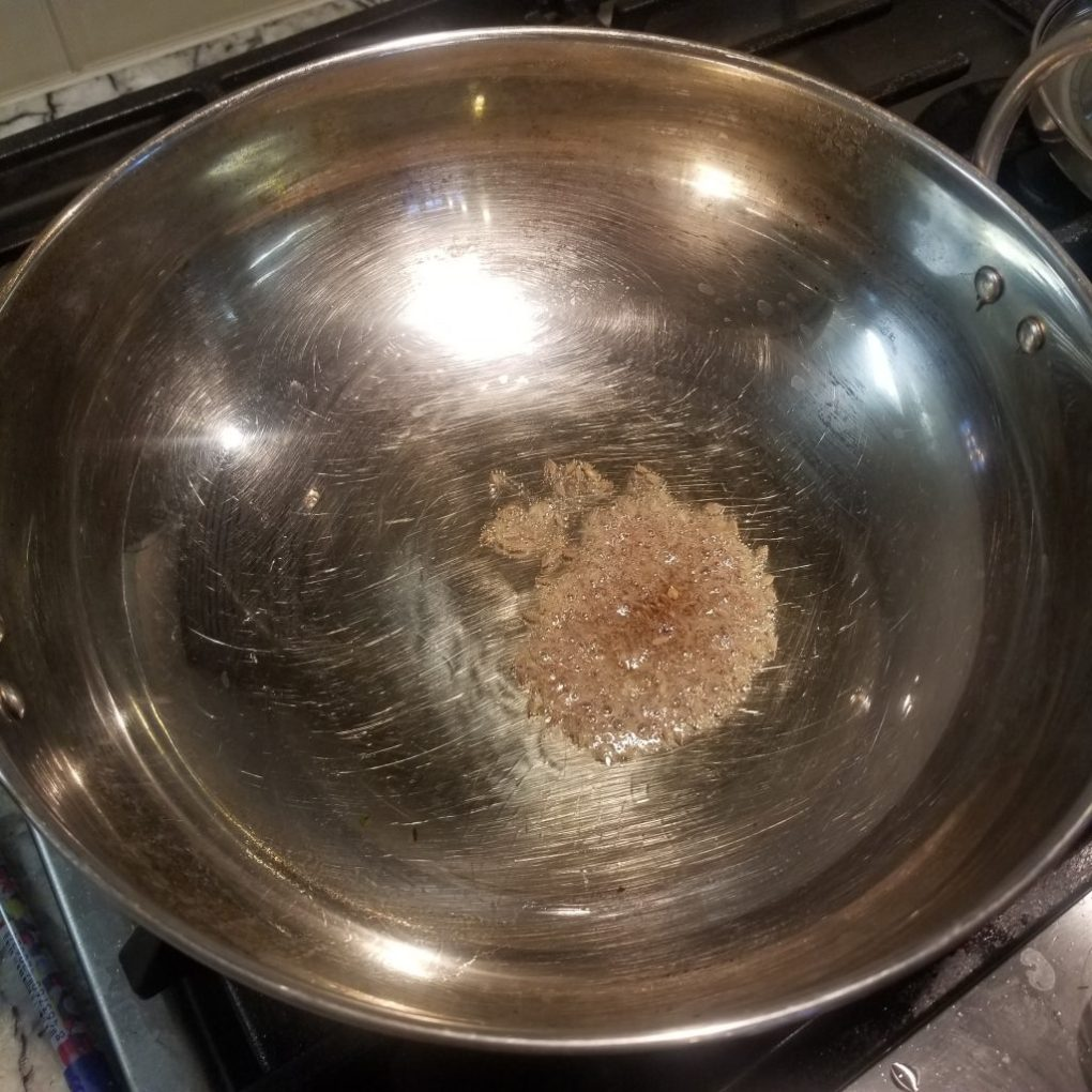 oil in a wok with cumin seeds