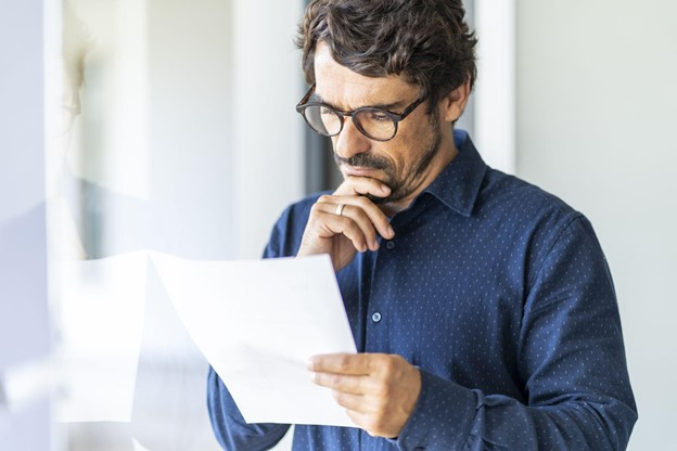 Man Looking at a Document To See If it Is a Real Birth Certificate