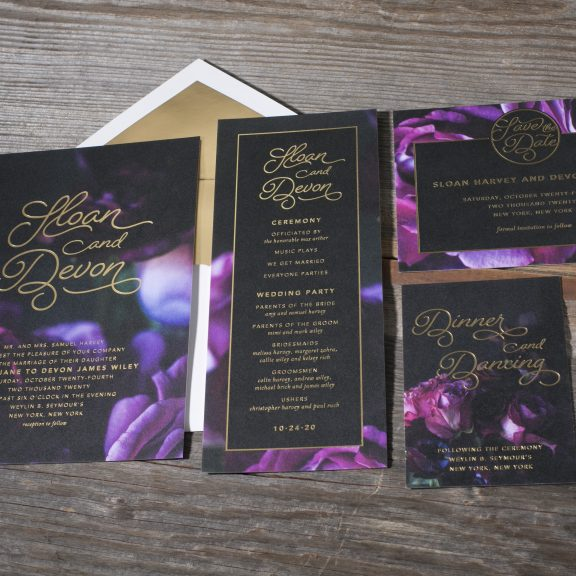Sloan by Bella Figura, modern floral and foil wedding invitation suite, black and purple floral background with gold foil text, calligraphy style font, modern, matching ceremony program