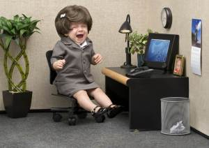 Female toddler dressed in suit sitting at office desk crying.