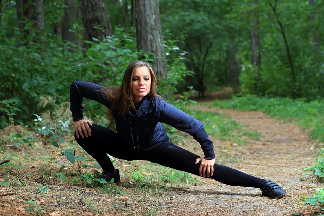 Woman on a forest path dressed in black stretching in a difficult position
