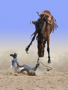 Bucking horse in the air above a cowboy that is on his face on the ground.