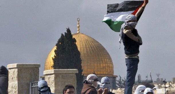 Palestinian stone-throwers gesture toward Israeli troops during clashes in East Jerusalem