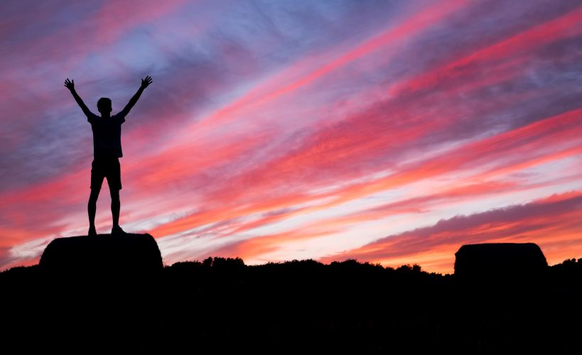 A silhouette of a man lifting up his hands while while standing on a rock at sunrise.