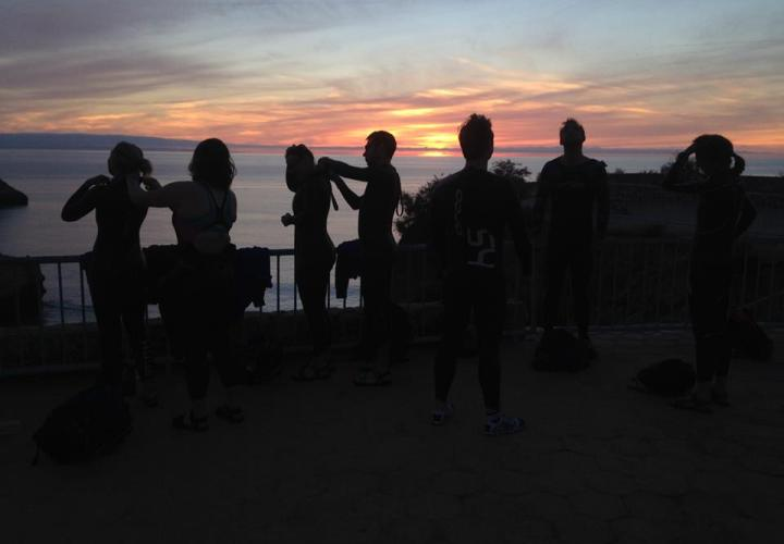 Silhouettes of swimmers doing up each others' wetsuits