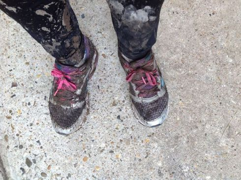 Very muddy trainers with pink laces.