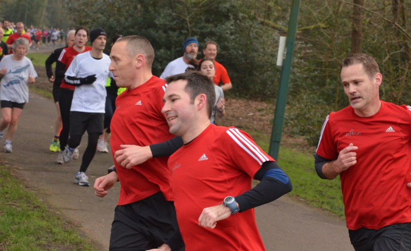 Stu, John and Rob all in red parkrun 50 t-shirts, black long-sleeved base layers and black shorts
