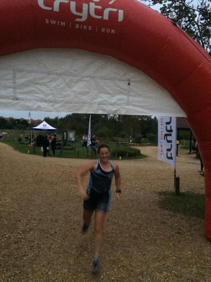 Tamsyn crossing the finish line at the aquathlon.