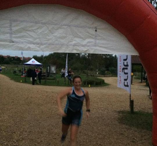 Tamsyn crossing the finish line at the aquathlon.