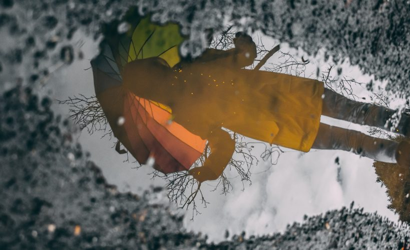 Reflection in a puddle of a person holding an umbrella