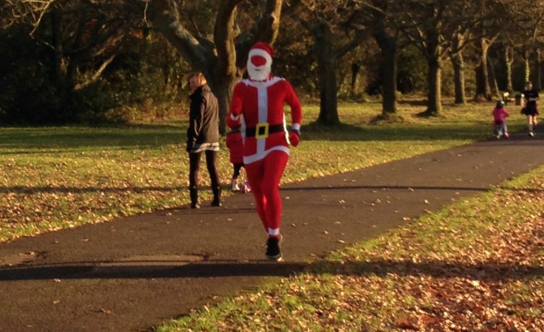 A man running in a Santa morph suit.