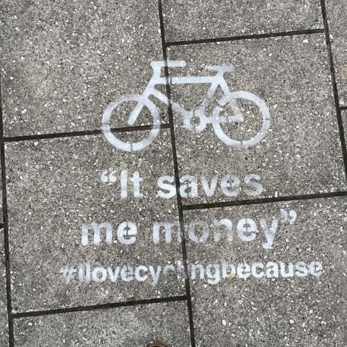 "Stencil on pavement saying ""I love cycling because it saves me money"""