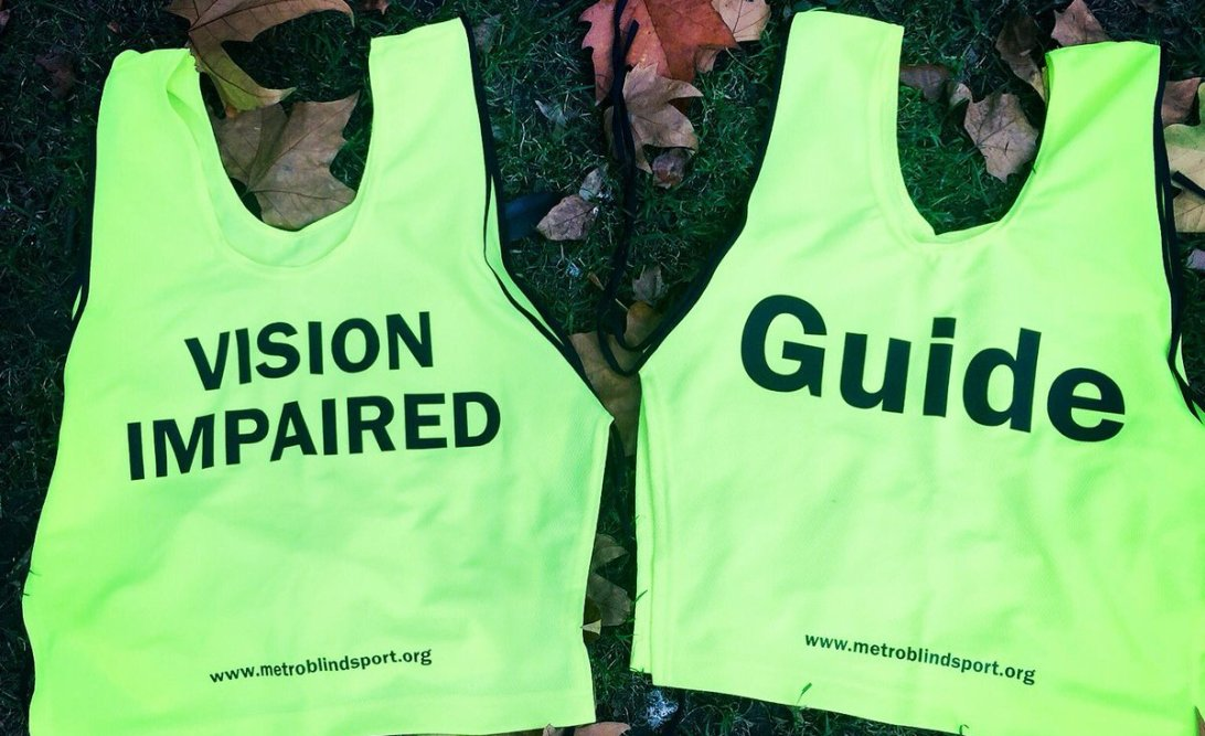 Guide runner vest next to a VI vest