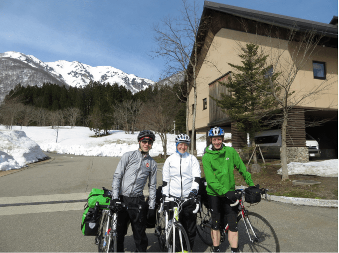 Stuart, Tamsyn and Jez outside the Shirakawa Go Eco Institute on their bikes. Deep snow can be seen.