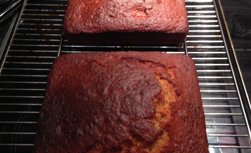 Two loaves of banana bready cake on a cooling rack.