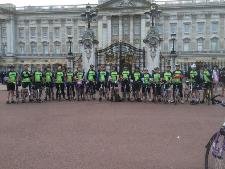 Large group of cyclists wearing YMCA jerseys standing in front of Buckingham Palace.