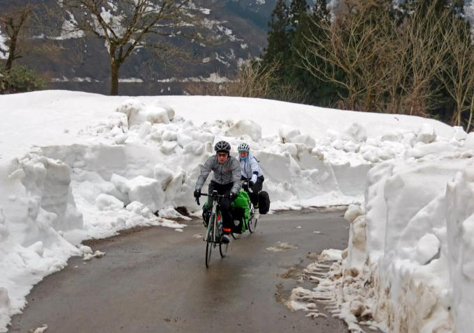 Tamsyn and Stuart cycling on a road with huge snowdrifts either side.