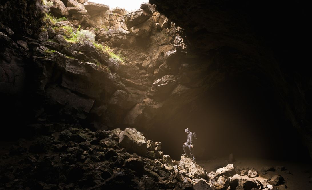 Person in a cave with light shining on them